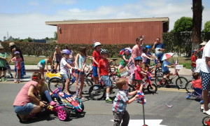 Josiah in the Fourth of July Parade. Josiah is in the center of the picture wearing a red shirt and sitting on a bike with green handle bars. Click photo for full size.