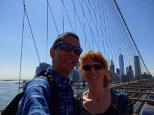 Selfie of Tim and Jeri on the Brooklyn Bridge with downtown Manhattan in the background. Click photo for full size.