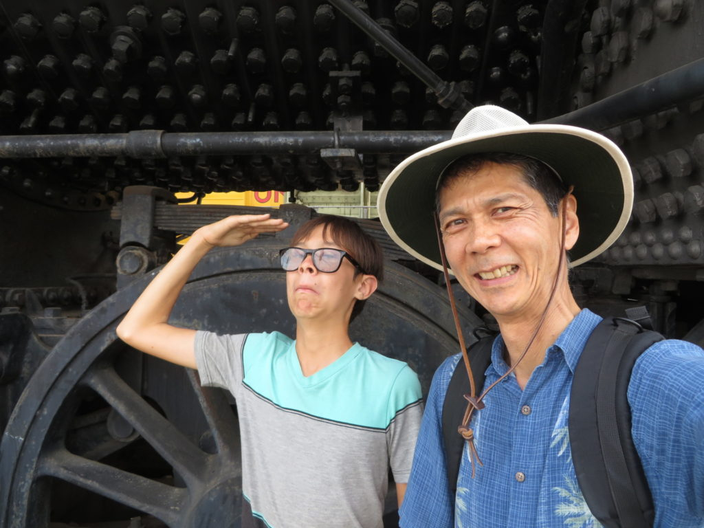 Josiah and Tim standing next to the wheel of a steam locomotive